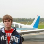 Picture of Jesse with his plane in the background